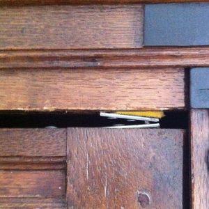 schade aan kastdeur o.a. door krimp aan achterzijde en verkeerd stellen van de kast